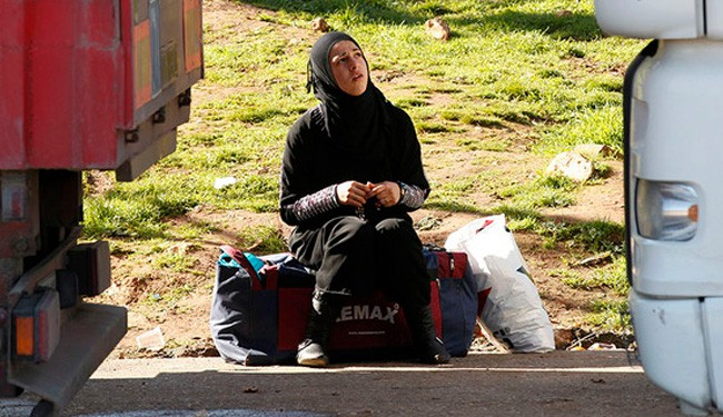 A Syrian woman waits for the gate to open at the Cilvegozu crossing near Reyhanli at the Turkish-Syrian border, Feb. 13, 2013.