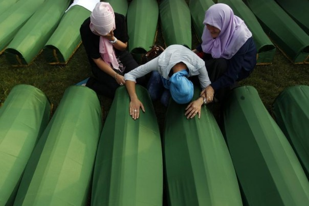 Bosnian women cry near a coffin of their relative, which is one of the 409 coffins of newly identified victims from the 1995 Srebrenica July 10, 2013. REUTERS/Dado Ruvic